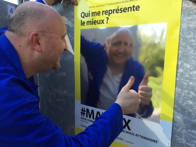 Les passants peuvent se voir dans le reflet déformant des affiches, ici lors du collage le 2 mai. (photo Ma Voix / Facebook)