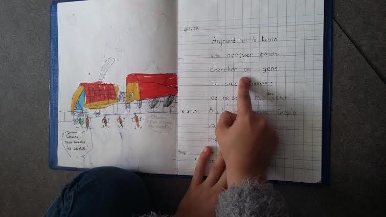 """Elisa lit fièrement son histoire préférée dans son """"cahier d'écrivain"""". (Photo IM / Rue89 Strasbourg)"""
