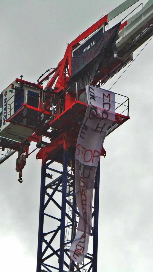 """Deux mamans sont montées en haut d'une grue et y ont placé des banderoles affichant les messages """"En Marche pour l'école"""" et """" école stop sabotage"""" (photo RG / Rue89 Strasbourg)"""