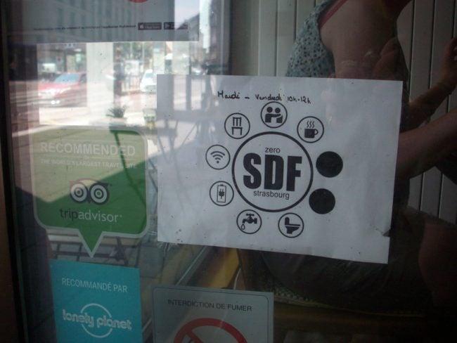 Le sigle de l'initiative Zéro SDF permet de renseigner sur les micro-services accessibles dans les commerces qui l'affichent, comme ici à Oh My Goodness, qui ne s'arrête pas aux cafés (Photo DL/Rue 89 Strasbourg/cc)