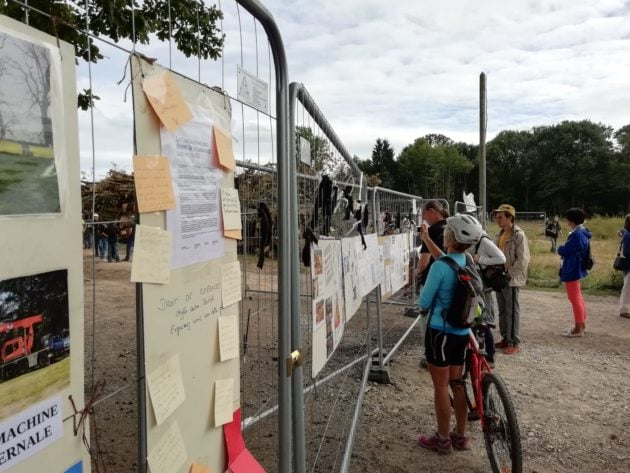 Les manifestants sont invités à laisser un noeud noir ou blanc aux grilles du chantier, en hommage aux arbres abattus. (Photo N. S.)