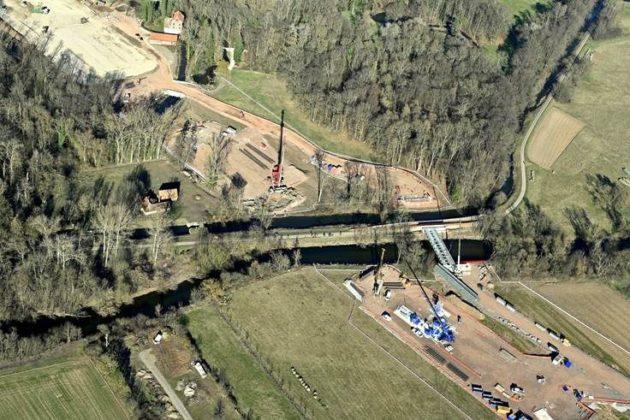 Sur cette photo aérienne du chantier du viaduc de Kolbsheim on voit la Bruche et son canal parallèle (en noir, avec la piste cyclable entre les deux), qui matérialise la limite avec Ernolsheim-Bruche. Tout en haut, on aperçoit le Moulin et sa grange. (photo Arcos)