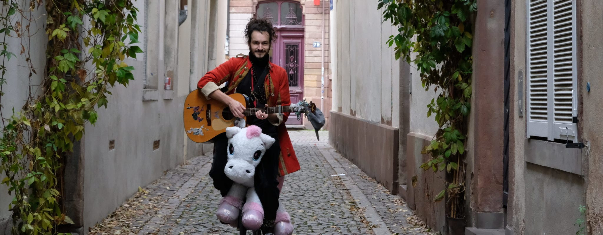 En lutte contre la morosité, Baptiste Schohn joue de la guitare sur un monocycle-licorne